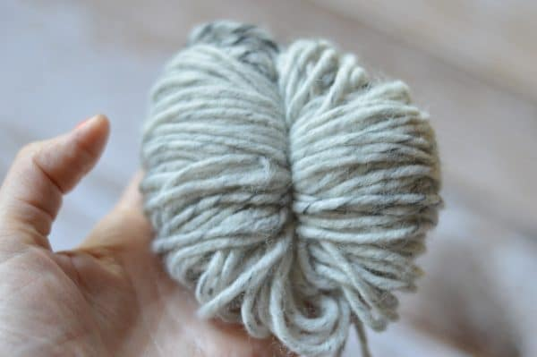 Tied wrapped yarn making a pom-pom