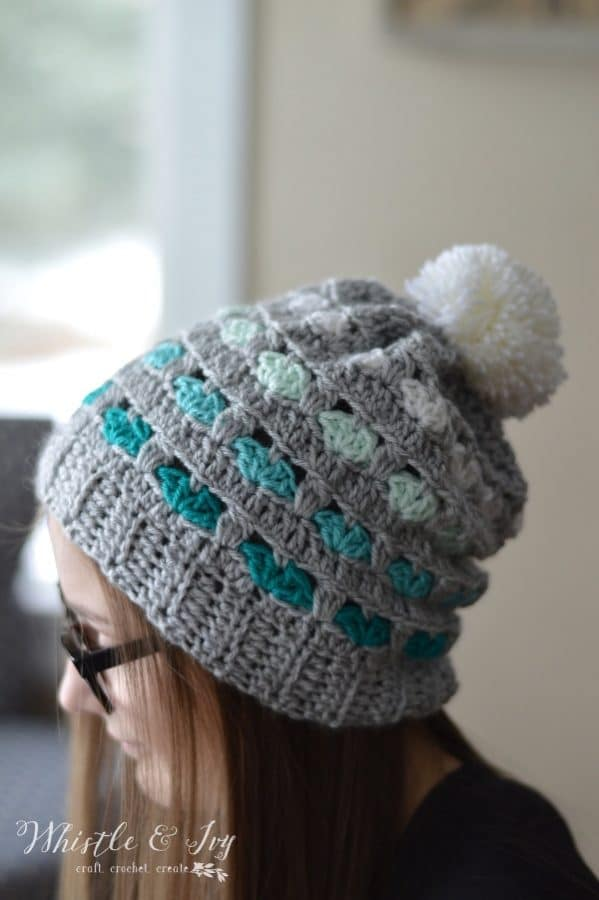 crochet crochet pattern for a crochet slouchy hat with hearts and an ombre color palette with yarn pom-pom on top.
