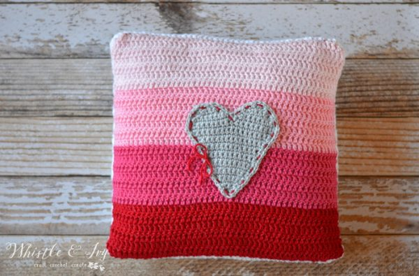 crochet pillow with ombre color palette from red to light pink and heart sewn on the front