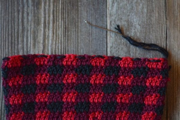 running stitch across the top of a buffalo plaid hat