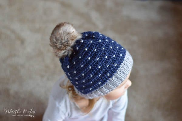 Child wearing navy blue crochet hat with fur pom-pom and a heart knit stitch pattern.