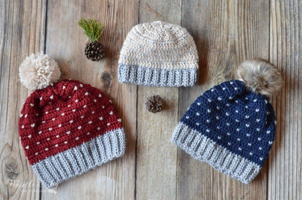 Three crochet hats with 3 different sizes, with yarn and fur pom-poms with heart knit stitch patterns.