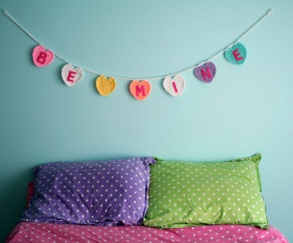 "crochet conversation hearts garland spelling ""Be Mine""."