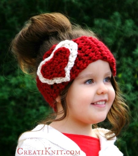 Smiling girl wearing a crochet red and white heart headband