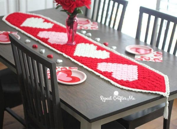 red crochet c2c table runner with pink and white hearts and tassels on the ends
