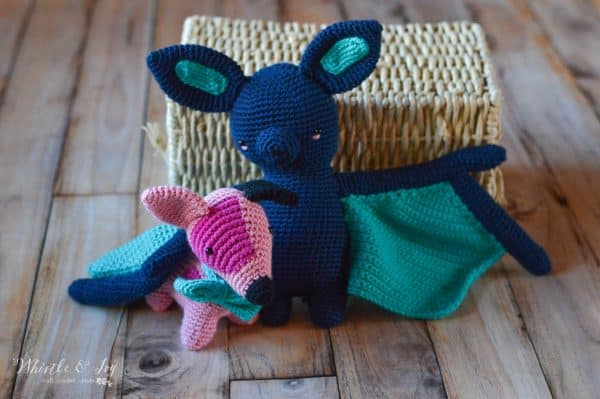 crochet bat sitting with wing over pink crochet puppy sitting in front of a basket