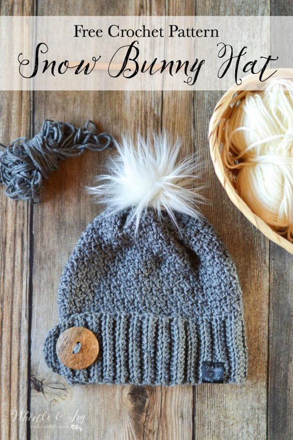 Crochet hat with large button and white fur pom-pom on top