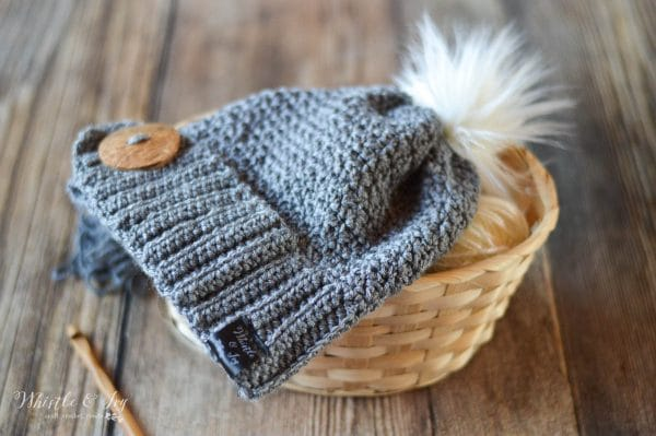 Crochet hat with large button and white fur pom-pom on top and a satin tag