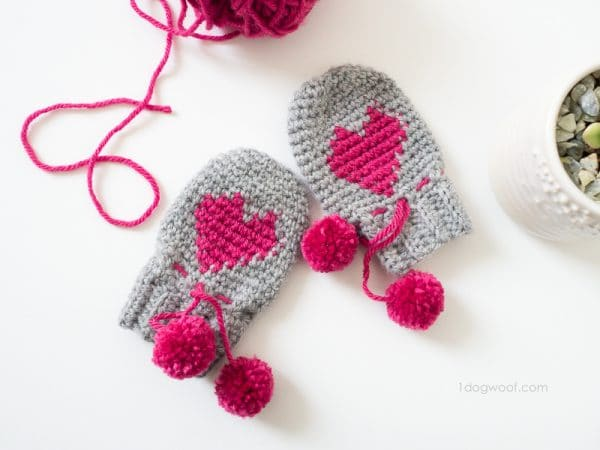 Crochet gray baby mittens with a pink heart on each mitten
