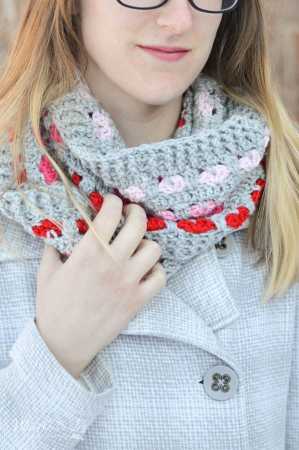 woman wearing crochet infinity scarf featuring pink and red hearts