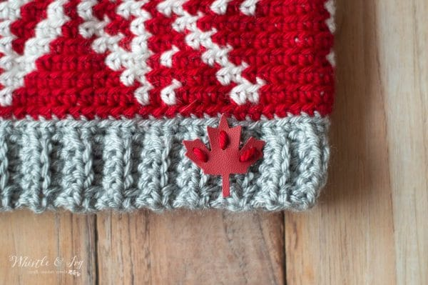 red and white hat featuring leather red maple leaf