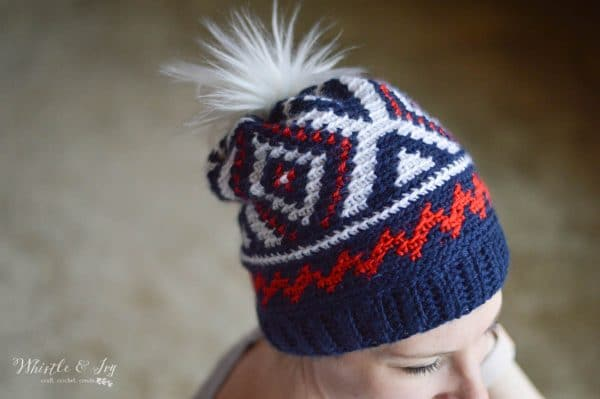 woman wearing olympic team crochet hat with red white and blue color work with fur pom pom