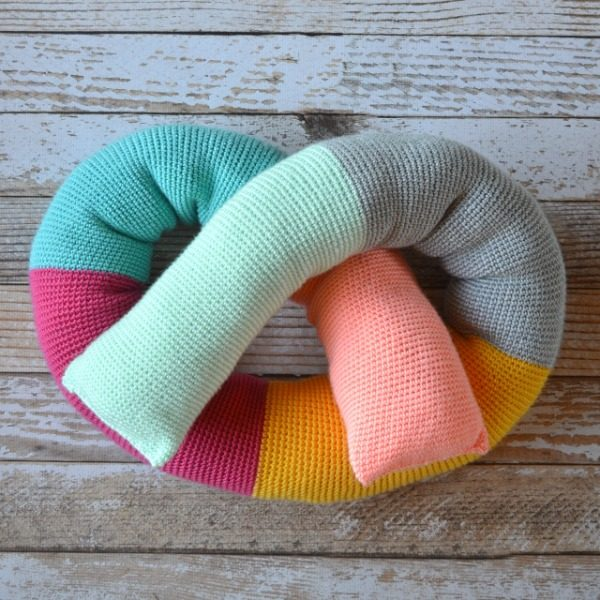 brightly colored crochet pillow shaped like a pretzel