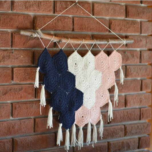 crochet hexagon wall hanging on brick wall with tassels