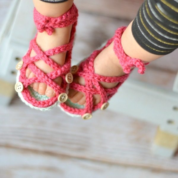 baby feet wearing crochet gladiator sandals with buttons