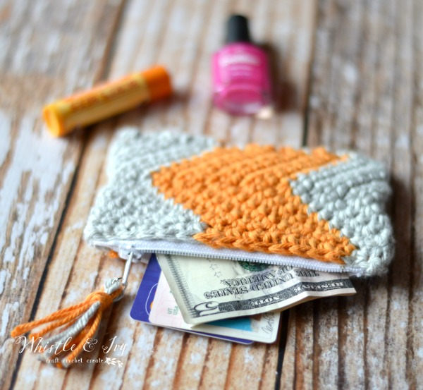 orange and gray chevron pouch containing money and cards