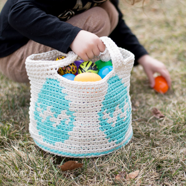 girl holding crochet Easter egg basket picking up an egg