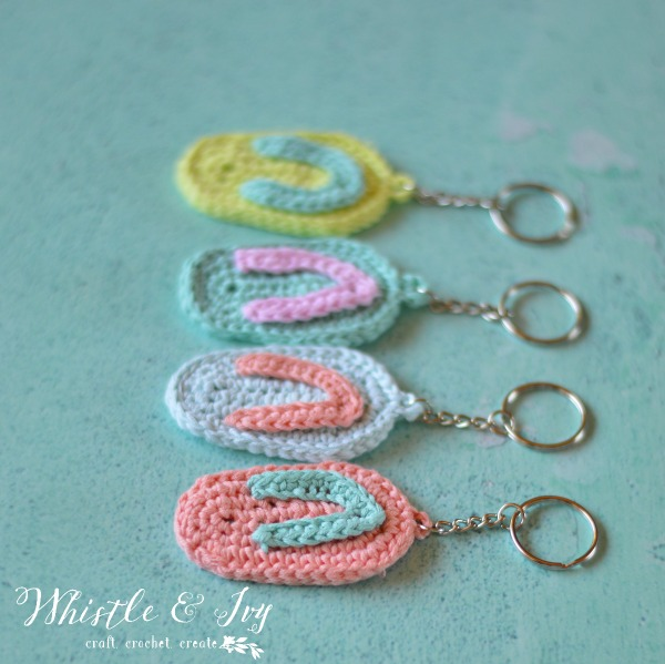 brightly colored crocheted flip flop key chains on aqua background