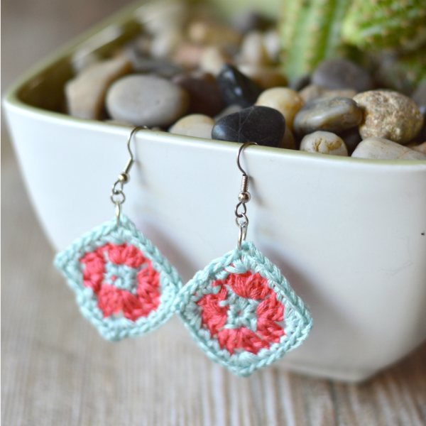 small crochet granny square earrings hanging on a bowl with rocks in it