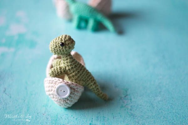 green crochet hatching dinosaur t-rex standing in a crochet egg with button
