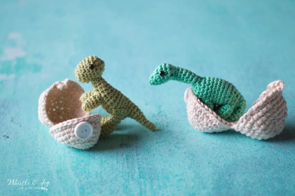 two small crochet hatching dinosaurs standing in crochet eggs