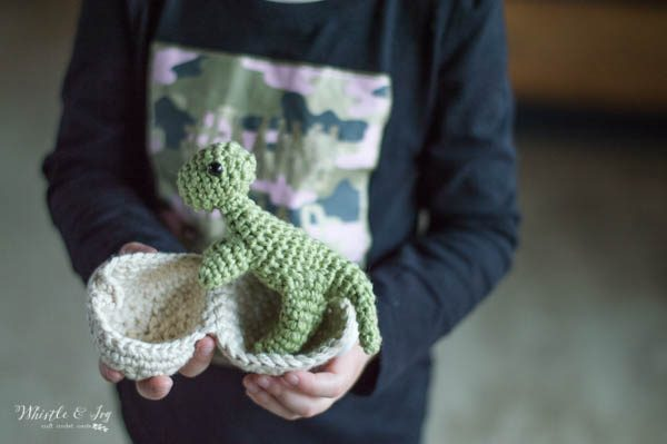 child holding a crochet hatching dinosaur t-rex standing in an egg