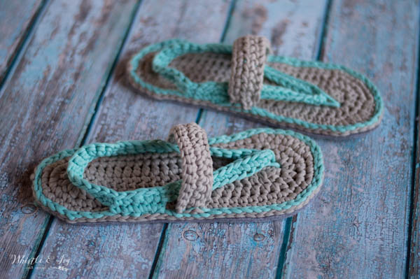a pair of women's crochet flips flops sandals on a wood floor