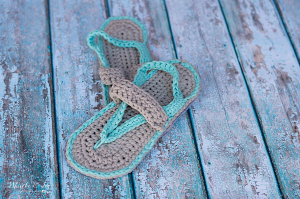 a pair of blue and gray women's crochet flip-flops