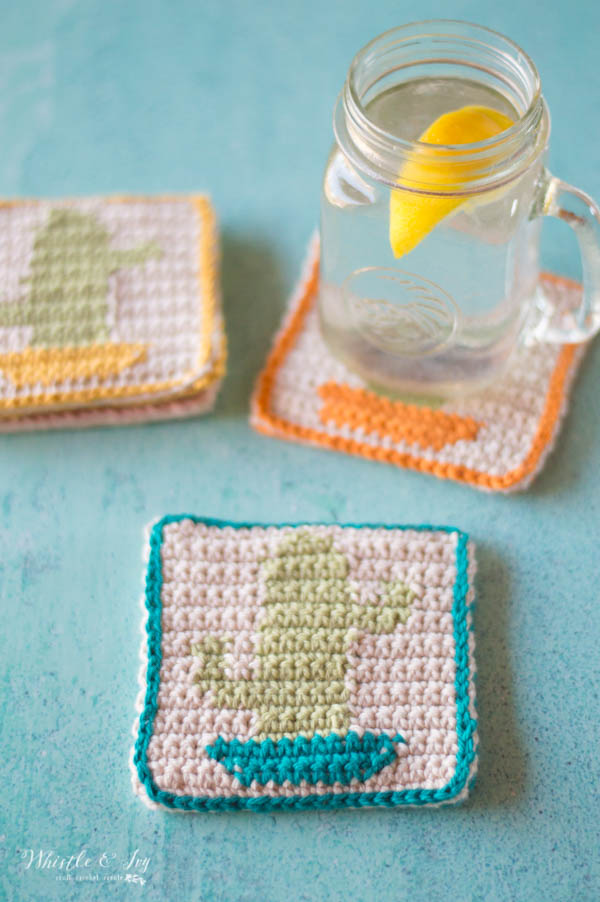 crochet cactus coasters on blue surface with lemon drink