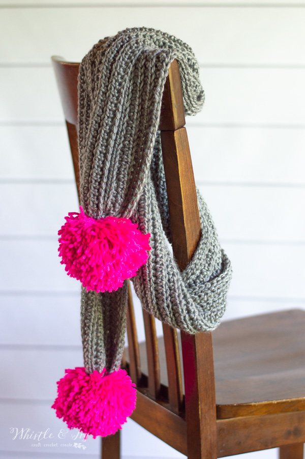 crochet pom-pom scarf hanging on chair