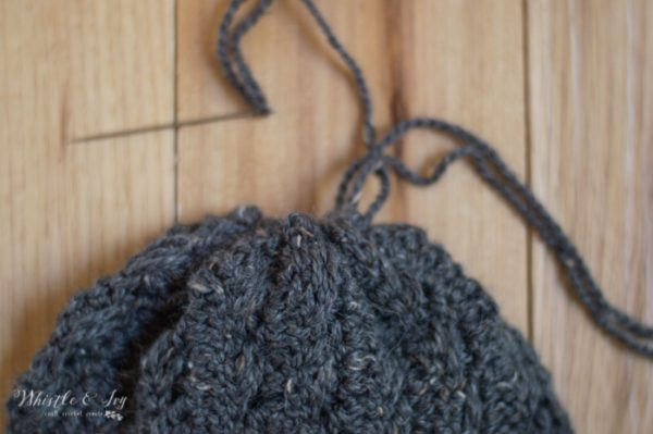 cinching the top of a crochet faux cable hat shut